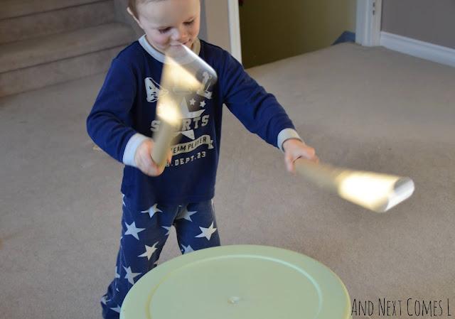 Preschooler playing DIY bucket drums