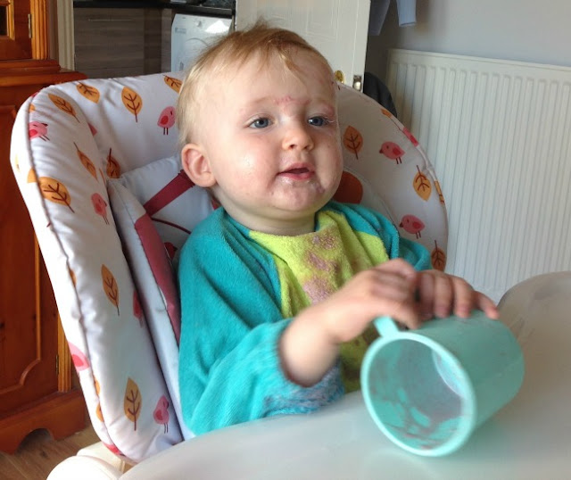 Toddler in highchair with empty cup and contents on his face and bib