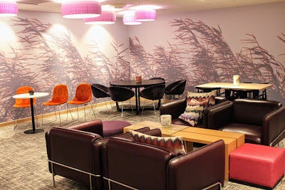 The natural lobby area with cozy leather chairs, round tables with chairs and a larger wooden table with chairs.