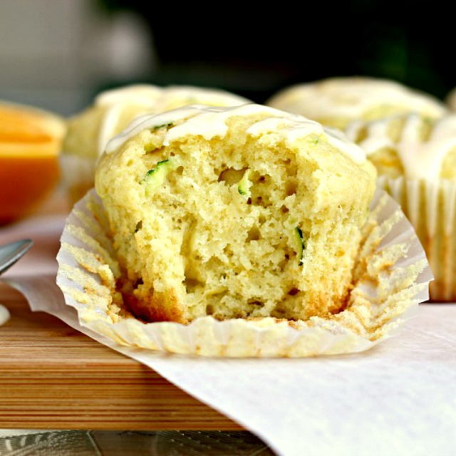 Glazed Orange Zucchini Muffins by Renee's Kitchen Adventures muffin on board with bite taken out so you can see flecks of zucchini inside and tender crumb