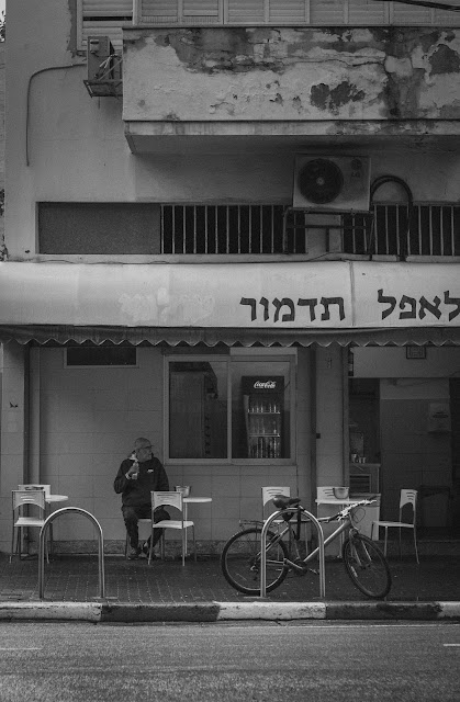 A man sitting with a bottle of water at a table in southern Tel Aviv