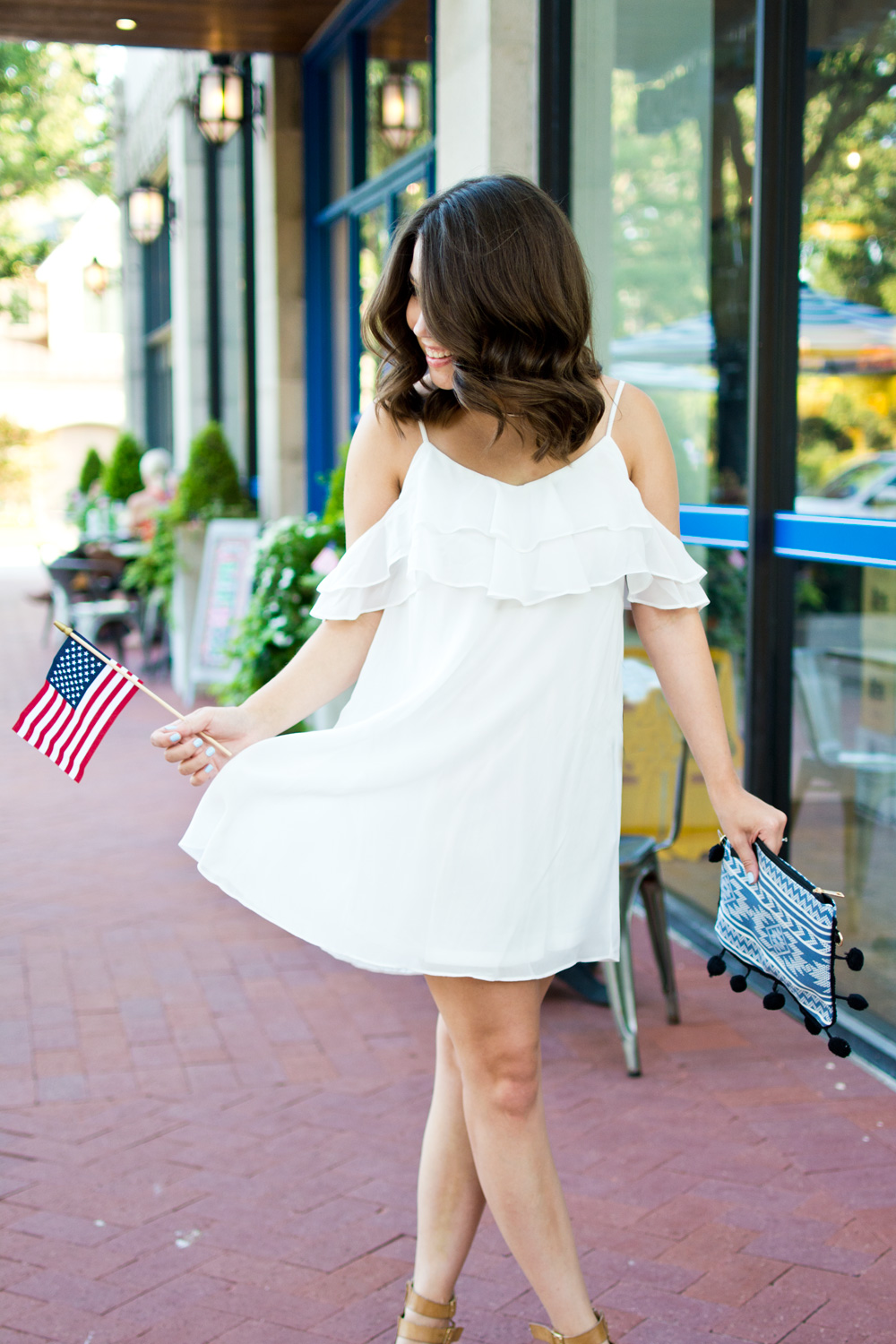 White cold shoulder sundress with blue pom pom clutch and American flag