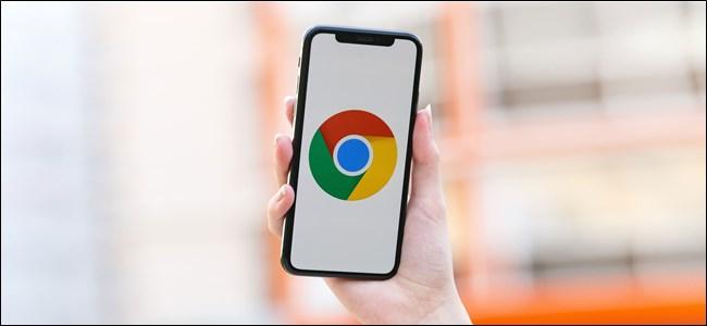 شخص ما يحمل iPhone مع ظهور شعار Chrome على الشاشة.