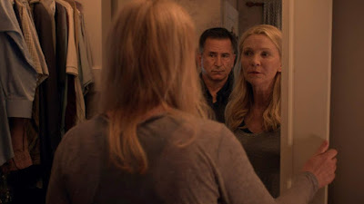 Stephen King's A Good Marriage 2014 movie still showing Anthony LaPaglia standing menacingly behind Joan Allen as she looks at him in the mirror