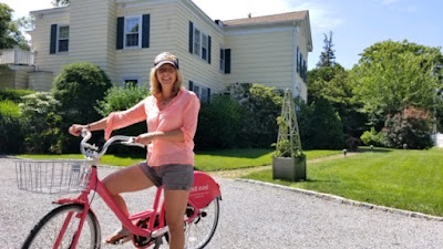 Woman on a bike in front of large Colonial house