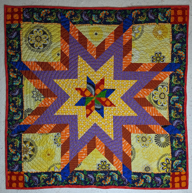 Blue, red, yellow, purple, and orange print fabrics create a modern Lone Star on a pale yellow background printed with large medallions. The navy border has lines of colorful geckos and the corners are posted with and orange on red batik.