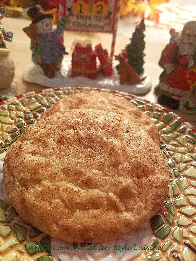 this is the best snickerdoodle cookie recipe with a pretty Christmas scene in the background. The cookies are on a christmas plate