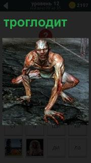 Изображение первобытного пещерного человека троглодит, который сидит на земле упираясь руками в землю
