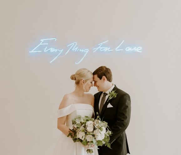 bride and groom in front of neon love sign