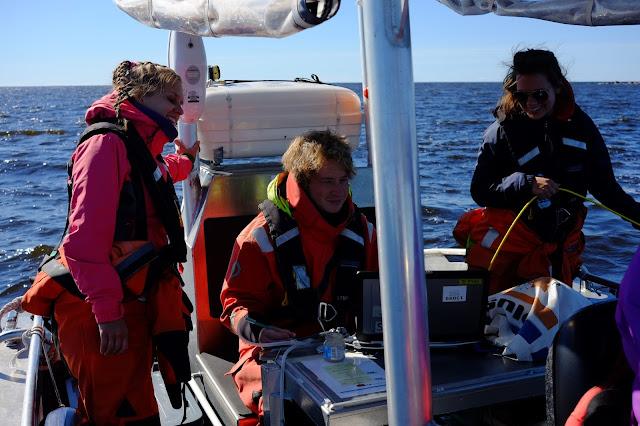 Kolme henkeä veneessä katsomassa drop-videolaitteistoa