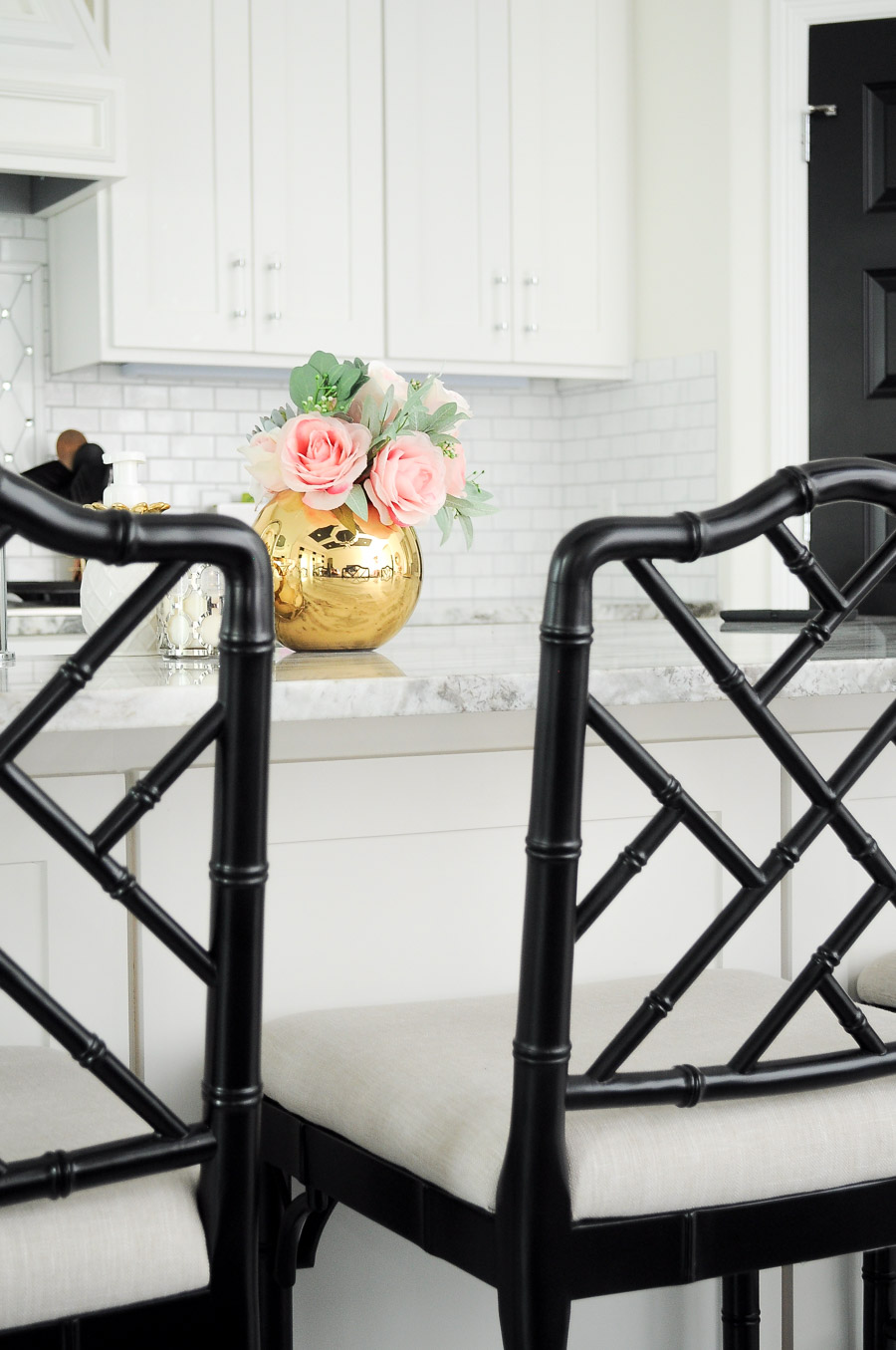 Black bamboo counter stools in an all white kitchen with a gold vase and florals.