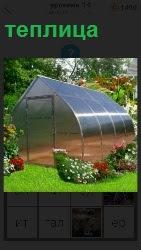 стоит теплица на садовом участке из поликарбоната