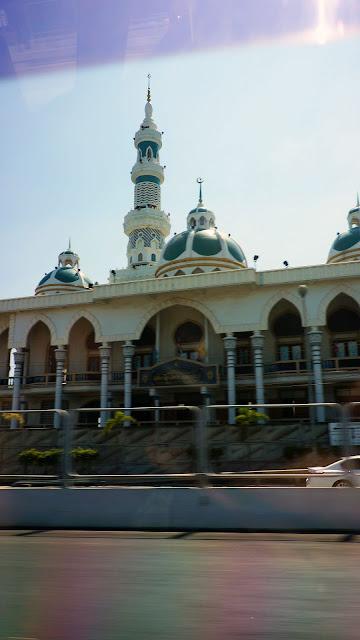 Изображение мечети, оставшейся позади такси