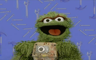 Oscar the Grouch appears with a jackhammer in his hands. Oscar then uses the jackhammer. Sesame Street Elmo's World Building Things Quiz