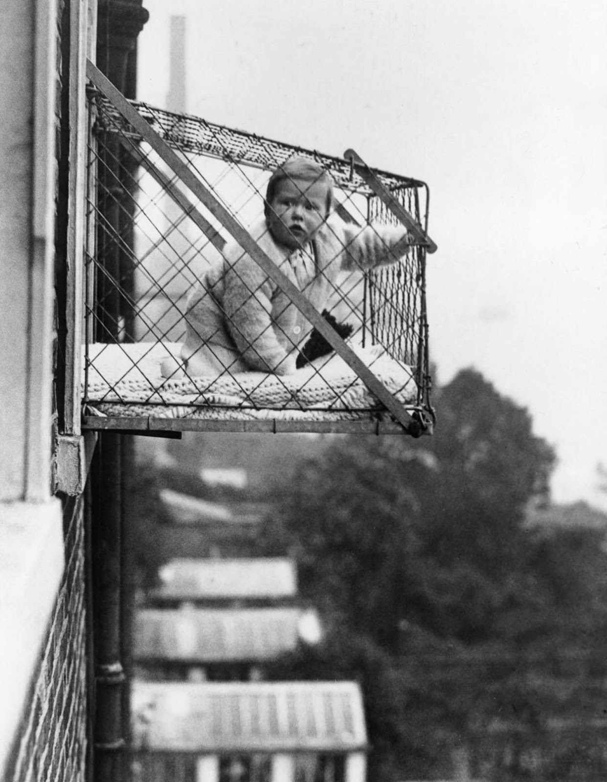 Responding to a lack of homes with outdoor space, people began outfitting windows with infant-sized cages for babies to hang out in. 1934.