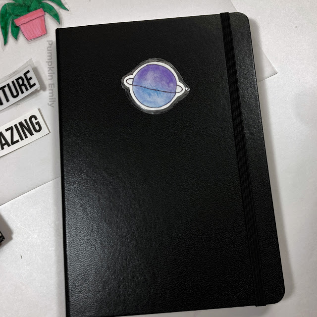 A watercolor sticker made with tape on a journal.