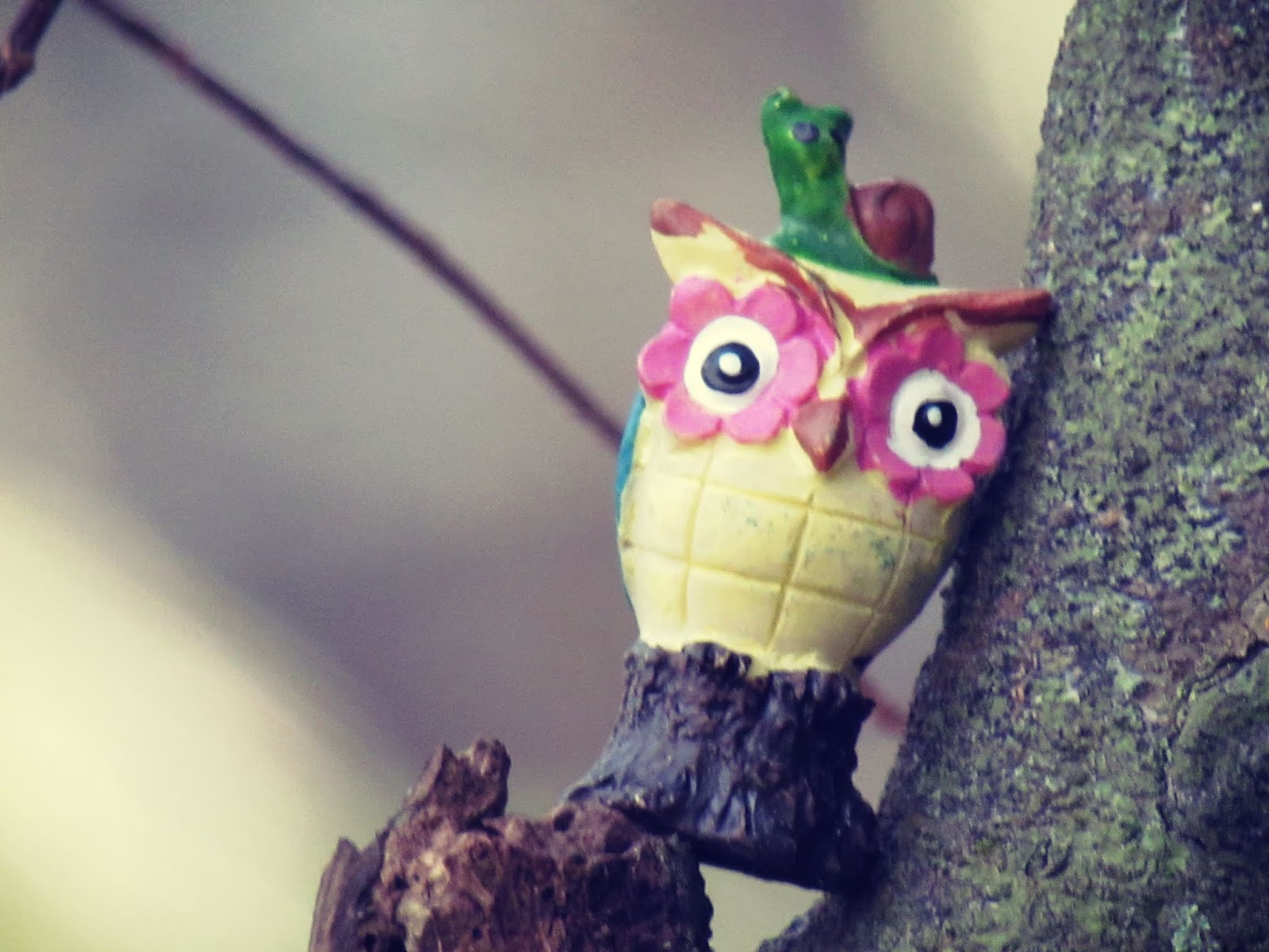 A tiny owl toy figurine up in a bare tree in winter in the magic of the forest