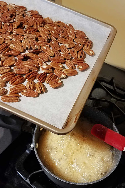 baking sheet of toasted pecans being dumped into saucepan of boiling honey
