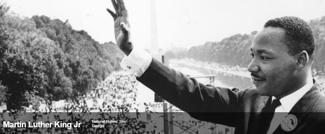 Image from the website for the Martin Luther King Jr. National Historic Site. Image shows Dr. King standing with an upraised arm at the National Mall with the Washington Monument in the background.