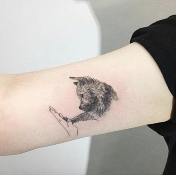 Foto de un tatuaje de yorkshire chocando la patita con su dueña
