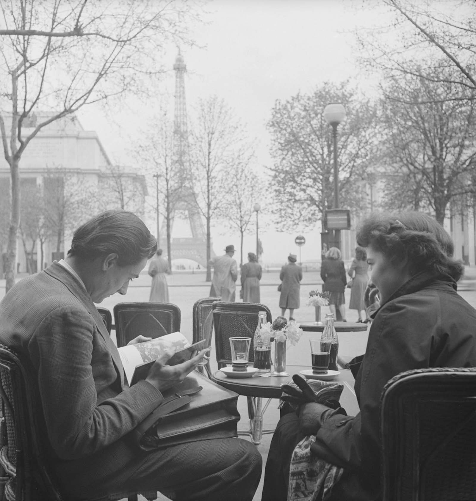 An unidentified couple sit at a sidwalk cafe near the Eiffel Tower and read. Each has a bottle of Coca-Cola in front of them.