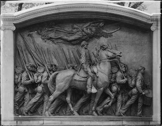 A relief showing a man on horseback surrounded by other on foot, all carrying bayonets. A draped female figure flies above them.