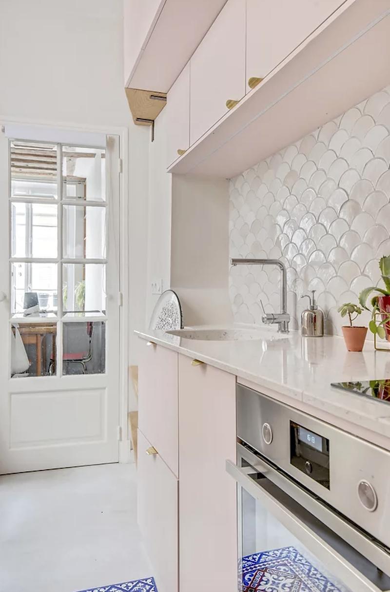 Cocina rosa con encimera de mármol y azulejos con forma de escamas de pez.