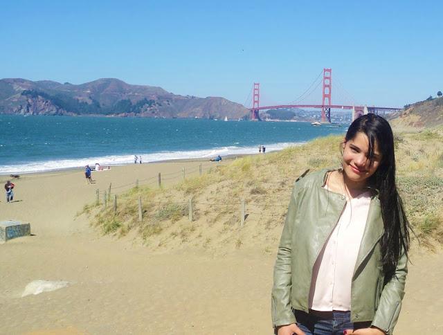 mulher na praia com a ponte golden gate vermelha ao fundo