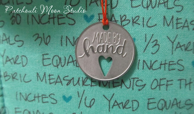 """closeup of metal tag that says """"made by hand"""" and depicts a cut out heart"""