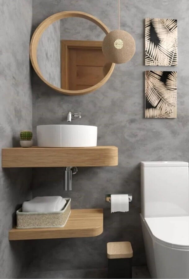 Small gray bathroom decorated with suspended bench and round mirror