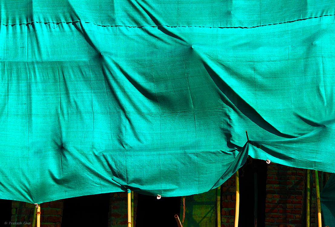 A minimalist photo of Building under construction covered by a green cloth.