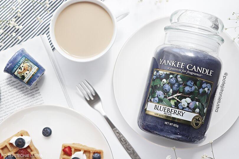 duża świeca yankee candle blueberry i sampler (votive) yankee candle blueberry scoone na stole z filiżanką kawy z mlekiem i pysznymi goframi z owocami