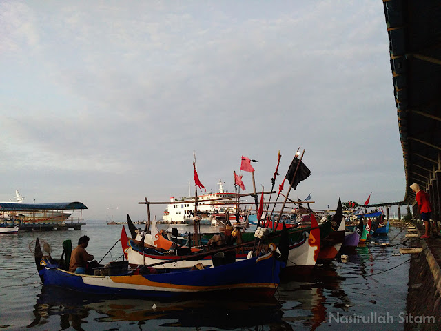 Para nelayan sibuk di perahunya masing-masing