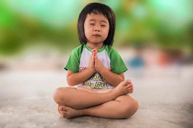 Ansiedade Infantil: Menino em posição de yoga e oração