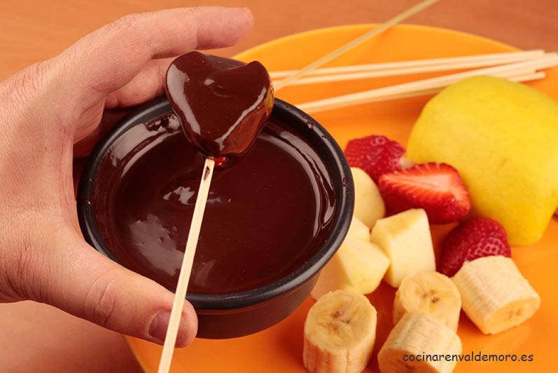 Sacando la fresa del chocolate fundido