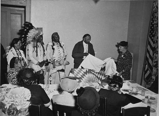 Tribal members present public health nurse Henrietta Crockett with a star quilt in recognition of her work to battle tuberculosis in Native American communities, 1949.