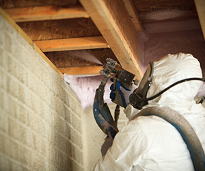 Installer Applying Spray Foam Insulation to Basement Sills, Protecting and Insulating Pipes; Foam Insealators of Maryland and Virginia