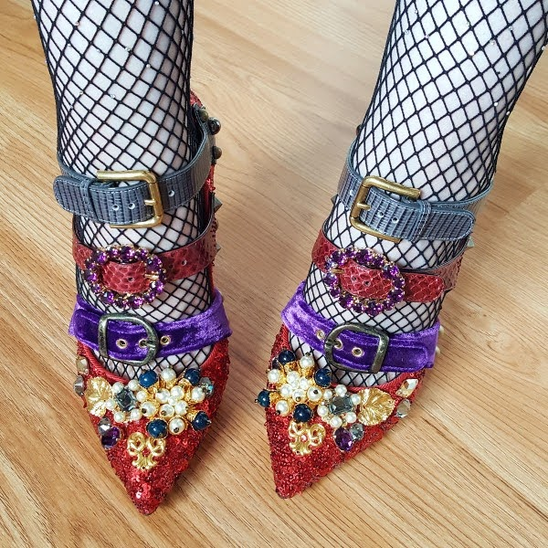 close up wearing pointed toe red sequins shoes with embellishment and multi coloured straps and buckles