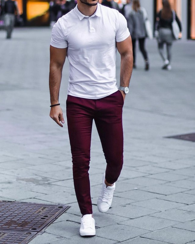 A man wearing white polo and maroon chinos.