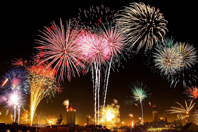 a city skyline with a firework display going off above it