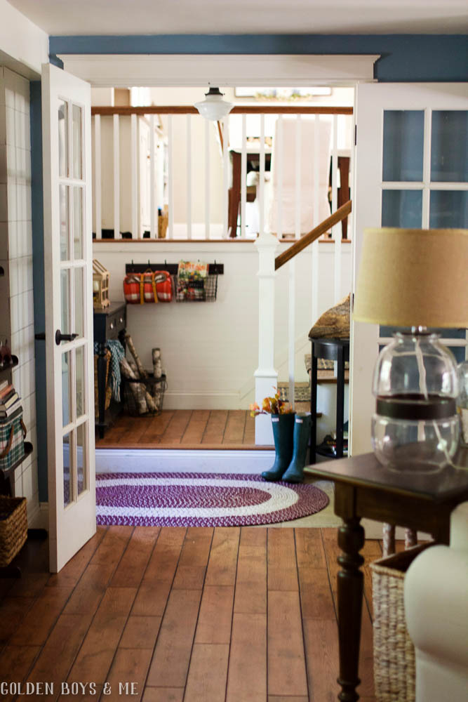 Split level entryway with fall decor including a braided rug to warm up a tile floor - www.goldenboysandme.com