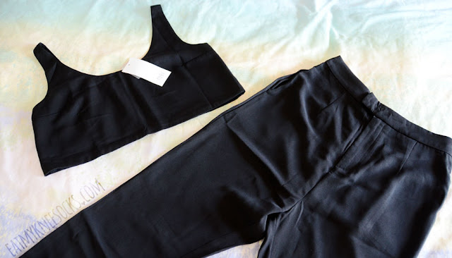 Details on the black two-piece Queen Bee set from Tobi, featuring a cropped sleeveless tank top and high-waisted tapered ankle trouser pants.