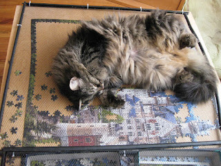 cat lounging on half-completed puzzle of Neuschwanstein Castle
