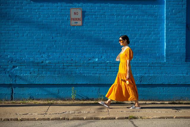 orange dress against blue bricks