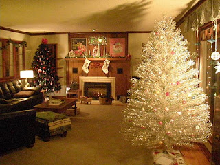 """A room with a real Christmas tree to the left rear next to fireplace and an aluminum tree in the right forefront"""""""
