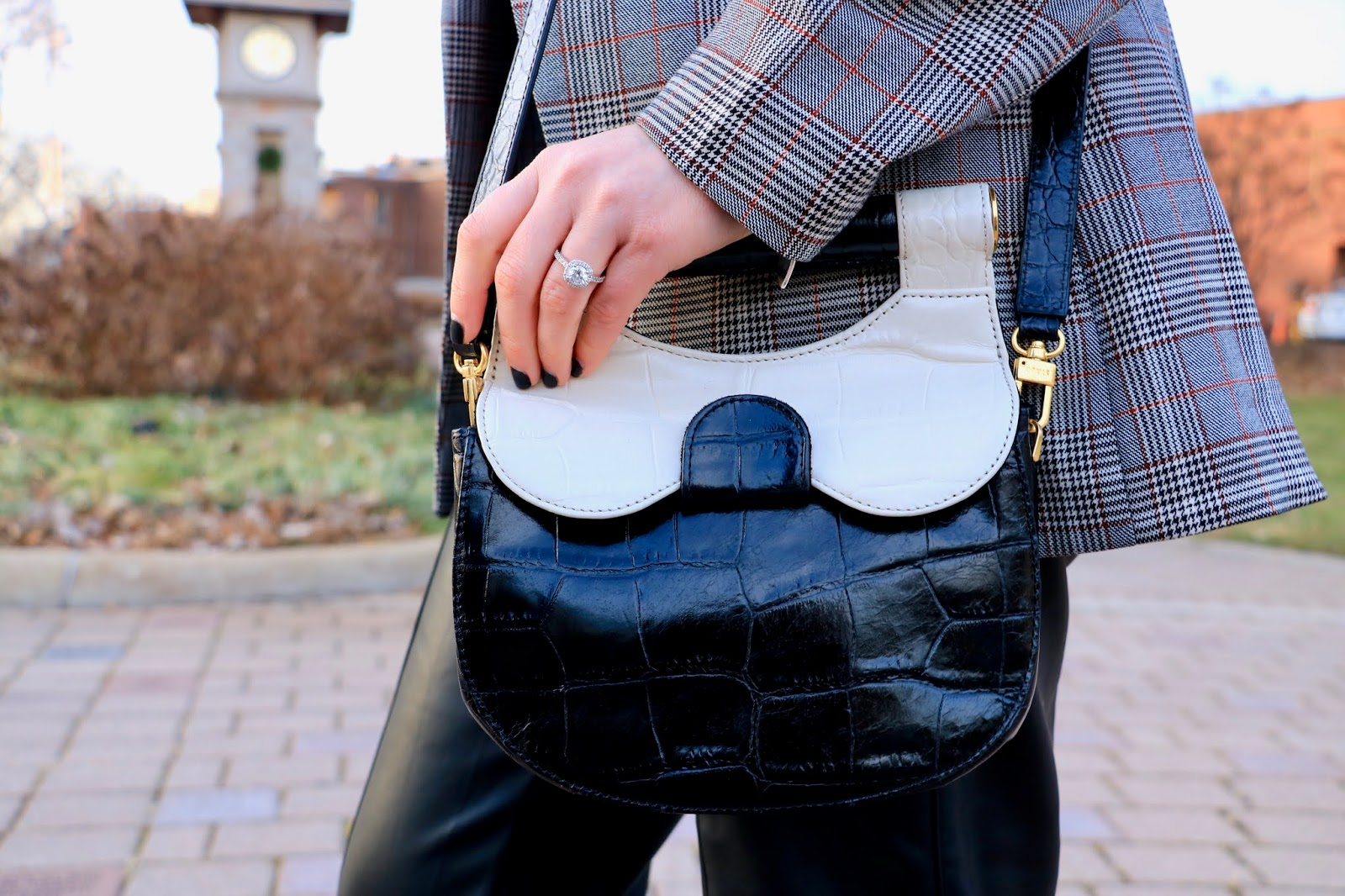 Nyc fashion blogger Kathleen Harper carrying a black and white Staud leather purse.