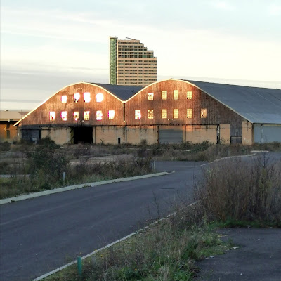 Photograph taken in late afternoon light. A single-lane private road leads to a warehouse, whose two gables are distinctively curved. Its first and second floors are of rusty corrugated iron, pierced with rows of windows. The ground floor storey is painted cream with large garage-type doors. In front of it and to the side of the road is bare soil interspersed with scrubby vegetation. Behind the warehouse, a high-rise block of flats is visible.