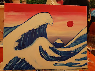 Simple red, white, pink and blue painting of a huge wave with a mountain and a sky and sun in the background.