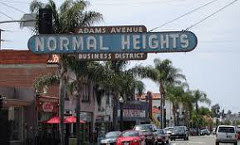 Across a large boulevard hangs a sign proclaiming 'normal heights.'