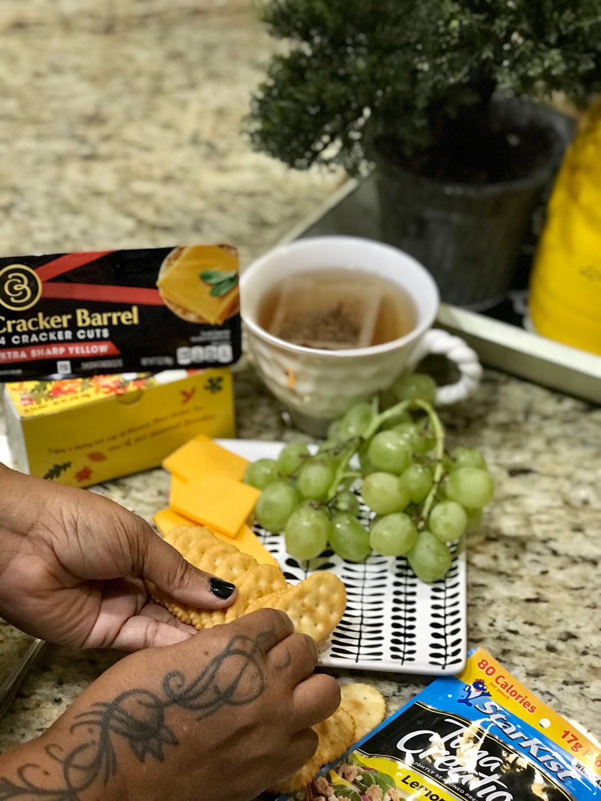 Making a tuna plate with grapes , cheese, crackers, and tea